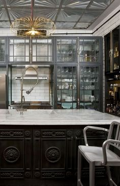 WOW! I adore those cabinets! Notice the subway tile (with dark grey grout) goes from floor to ceiling all around the room and even, BEHIND the glass cabinets. That's art deco tile on the ceiling. Beautiful.
