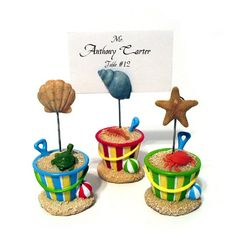 "These adorable beach bucket placecard holders are the perfect way to display your wedding place cards. They will also make a perfect favor for your guests to display their vacation photos once they get home. Each place card holder is made of poly resin and comes in 3 assorted colors and designs. Blue bucket with turtle, green with crab and red with lobster. Each place card holder measures 1 3/4"" x 3 3/4"" and holds a 2"" x 3"" placecard or photo.  #weddingfavor #placecard #beach #bucket #summer"