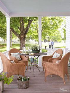 A small dining area in this porch provides a casual spot to enjoy a meal in the summertime. The contrast in materials between the wicker chairs and the metal dining table creates a relaxed and inviting atmosphere.