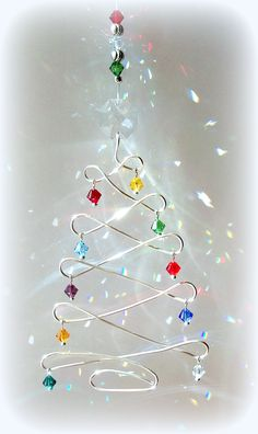This whimsical little Artisan Wire Christmas tree is sure to start your holiday season off with a sparkle.   Just hang this simple but colorful sun catcher in a sunny window and let the fun begin.  THIS IS AVAILABLE...PLEASE CONTACT ME.  IF YOU WOULD LIKE MORE THAN ONE,  PLEASE LET ME KNOW AND I WILL CREATE A CUSTOM ORDER FOR YOU.    I have fashioned a Christmas tree with silver-toned, tarnish resistant Artisan Wire.   Dangling from the branches are sparkling ornaments of 5mm Swarovski…