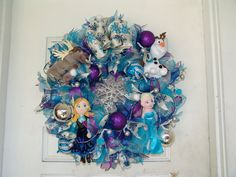 "Deluxe LIGHT UP Frozen Christmas Winter Deco Mesh Door Wreath Anna, Elsa, Olaf, Sven, snowflake. What a fun wreath for Frozen fans! The colors, the dolls, the bow, the glittery snowflake in the center, it's just gorgeous! Easily keep this wreath up all winter long, not just at Christmas time. Or if you're looking for Frozen Bedroom decor, this would look fantastic over a bed or dresser or even on the bedroom door! A great Christmas gift! The wreath is approximately 27"" in diameter. Full…"