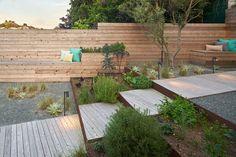 parquet chêne massif, clôture en bois, graminées d'ornement, marches en bois et coussins décoratifs