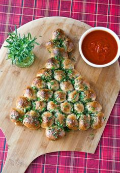 Christmas Tree Pull-Apart Bread: Turn your favorite cheesy bread dish into a Christmas tree-shaped treat! Topped with fresh basil, rosemary and a side of marinara, this recipe will be the hit of your holiday party. Find more easy, make ahead, healthy, elegant and classic Christmas dinner and party appetizers, finger foods and dip recipes and ideas here.