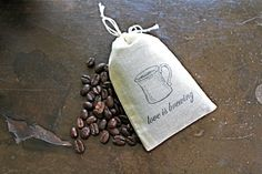 """Coffee favor bags, 2x4, hand stamped, set of 50, perfect for wedding favors  Darling muslin bags are the perfect finishing touch for your wedding or party favors! Drawstring bags are made from natural colored muslin and hand stamped with a coffee cup and the words """"love is brewing"""". Fill with coffee beans, chocolate covered espresso beans, or coffee candies!  Each bag holds about 1/4 cup of whole beans, approximately one ounce."""