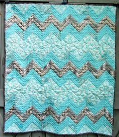 Aqua/grey chevron baby quilt with straight line and feather quilting.