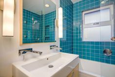 This bold bathroom features a neutral wood vanity paired with a large rectangular sink that boasts dual chrome faucets. Vibrant teal ceramic tiles cover the shower area, adding a splash of fun color.
