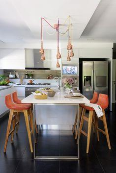 Cocina comedor integrados, en tonos blanco, naranja y cobre, con gran lámpara de cobre coronando la isla.