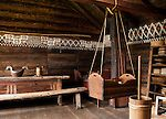 """The white chalk paint decoration on the wall is called """"kroting."""" A baby cradle hangs from ropes. On the right is a butter churn made of wood. The Medieval room reconstructs Norwegian lifestyle from hundreds of years ago. The Hardanger Folk Museum was founded in 1911 in Utne, Norway."""