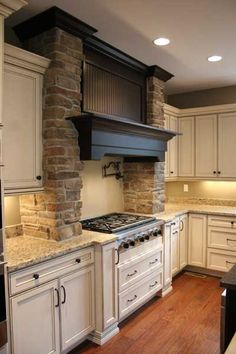 GORGEOUS KITCHEN!    Luxe Shasta Maple cabinets in alabaster with coffee glaze. Custom hood with cultured stone columns.