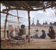 Navajo Indian Camp - Navajo Indian Reservation, Arizona. The woman works at her loom under the summer shelter, weaving a rug for which they are famous with some of her family about her. The red sandstone formation of The Yebechai (Twelve Dancers) stands on the skyline in Monument Valley, traditional home of the Tribe. :: Colorado Plateau Digital Archives Selections