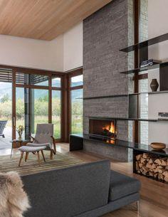 fenêtres bois, salon cosy avec fauteuil relax et repose pieds, habillage de cheminée en pierre naturelle et canapé gris