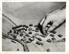 """1942- Student officers in the Armored Force School at Fort Knox study tactics with """"toys"""" on a 24-by-38-foot canvas replica of a slice of English countryside."""