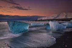 Stunning: A beautiful morning glow behind the ice blocks on a beach in Iceland. Photographer Lurie Belegurschi searches frozen north combs beaches for these incredible diamond-like blocks of ice