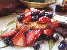 Stuffed French toast with blueberries and strawberries in honey glaze with sausage patties.