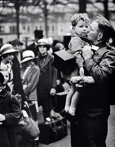 A soldier kisses his son goodbye as children are evacuated to the countryside, 1940. Stringer & Hulton