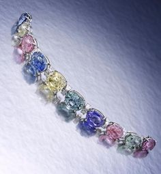 A multi-color sapphire and diamond bracelet, Bulgari, designed as a graduated line of oval-cut yellow, blue, pink, purple, green and colorless sapphires, largest yellow sapphire measures approximately 14.60 x 12.30 x 8.00mm, spaced by square-step cut diamond arched links; signed Bulgari; largest sapphire weighs approximately: 12.00 carats; estimated total diamond weight: 2.50 carats; mounted in platinum