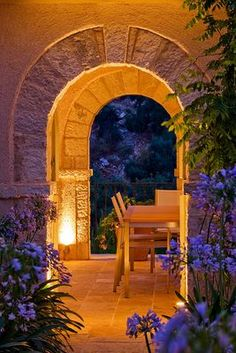 Corfu, Greece DESIGNER: DOMINIC SKINNER. MEDITTERANEAN STYLE GARDEN - VIEW THROUGH TWO STONE ARCHES LIT UP AT NIGHT WITH TABLE, CHAIRS AND AGAPANTHUS