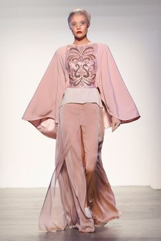 """Per una donna amante di un look """"romantico"""" e sofisticato, la Designer propone una gonna lunga rosa cipria aperta con uno spacco frontale, abbinata ad un mantello impreziosito da uno straordinario ricamo sul davanti e da maniche larghe. Le linee morbide di questo outfit donano classe ed eleganza a chi lo indossa."""