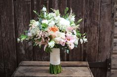 Delicate, rustic and whimsical bridal bouquet containing spring flowers, sweet peas, David Austin Garden Roses and Dicentra. Peach, white, blush pinks