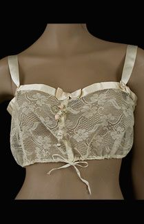 French lace camisole, c.1905. Made from delicate cream colored cotton lace and completely hand sewn, the camisole closes in front with hidden snaps. The fullness can be adjusted at the bottom with the ribbon drawstrings. The shoulder straps and upper border of matching satin ribbon are decorated with small bows.