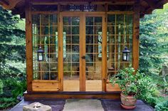 gorgeous exterior, hanging lanterns, lots of wood and glass surrounded by nature