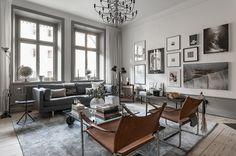 Gråskala och designklassiker i vacker sekelskiftesvåning