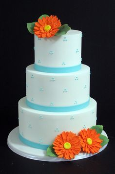 Blue dots and orange sugar daisies add fun pops of color to this light blue cake.