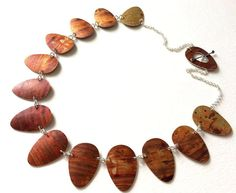 Beautiful necklace made from dyed aluminium and silver. It takes it's inspiration from a rusty painted door.