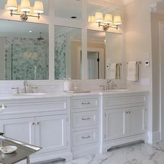 White Master Bathroom Features Double Vanity Topped With Marble Framing His And Her Sinks Under Framed Mirrors Illuminated By Restoration