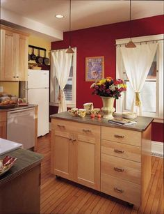 Laminate counters with metal edging and bright red and yellow walls lend a retro feel to this cheerful kitchen.