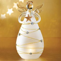 "Add a bit of grace to your holiday decor. Elegant angel centerpiece to put on mantle or tabletop. Lights up using 2 button-cell batteries (included). 7"" H x 3 1/2"" diameter. Glass. Imported."