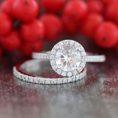 This halo diamond wedding ring set showcases a halo engagement ring with a 7x7mm round shaped natural white topaz crafted in a solid 14k white gold