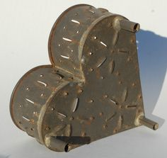 """Antique Tin HEART SHAPED CHEESE MOLD--Footed Base--NICE sold 235.00  This is a very nice antique tin HEART SHAPED CHEESE MOLD with attractive punched pattern and soldered on feet. 6"""" across, 6"""" from front to back, 3"""" high. Condition good."""