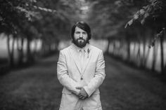 """The beard is in! And this groom is rocking it with his long dark locks! This light colored three-piece suit was a perfect blend of vintage, casual, and elegance; just enough """"WOW"""" to match, but not out-shine his beautiful bride! The sprigs of lavender were a perfect balance of color and style sitting right on the lapel of his jacket. Photo Credit: Scott Stebner Photography"""
