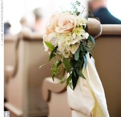Small clusters of creamy white roses and hydrangeas dressed up each aisle of the chapel.