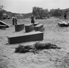 Dutch forensic technicians are exhuming the remains of 104 resistance fighters shot by the Germans, and buried in a common grave near the town of Overveen, May 5, 1945, in order to give them a proper burial. Coffins are at hand. Note the armed guard on the right background of the photo.