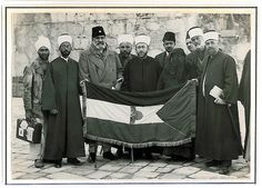 Hajj Amin (center) presenting Palestinian flag to Mawlana Shawkat Ali, (left of Hajj Amin) a leader of Indian Khilafat movement; next to Shawkat Ali is Shaykh Khwaja Nazir Hasan Ansari, 1931. © Ahmad al-Ansari.