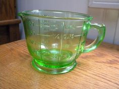 Cute old green glass measuring cup.