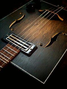 4 string cigar box guitar with f-hole cutouts and humbucker pickup.