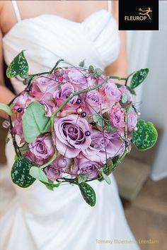 In dit rond gebonden bruidsboeket is gebruik gemaakt van roze/paarse rozen. Voor de speelse accenten is gebruik gemaakt van de Scindapsus Pictus en zijn parels in verschillende kleuren gebruikt. Dit trouwboeket gemaakt door Tommy Bloemen uit Leerdam is echt een plaatje! All Flowers