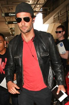 Bradley Cooper kept it cool in a leather jacket, backwards baseball cap and classic aviator shades post-flight in Los Angeles.