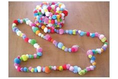 ...garlands of pom-poms.  How cute would these be to drape across ceilings?  Check out the too cute tutorial.