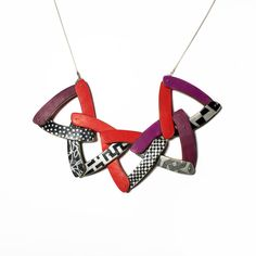 Triangle Crescent Necklace by Louise Fischer Cozzi. Red, purple, black, and white patterns make up the crescent beads on this necklace. The crescent beads are then put together with fine silver into triangles, then interwoven and attached to a sterling silver chain with a series of sterling ovals to make the necklace adjustable.