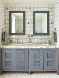 Contemporary bathroom features mini-subway tiled nook filled with blue wash, beveled mirrors over blue wash, double vanity topped with white and grey marble ...