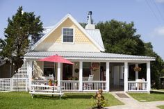 House in the hill country with wraparound porch and attic window.