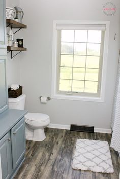 Barn wood style vinyl plank flooring is the perfect foundation for Must Have Mom's farmhouse bathroom makeover. Click this pin to see the full transformation!