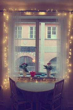 Sheer white curtains with Christmas lights! Love this idea for a little breakfast nook!