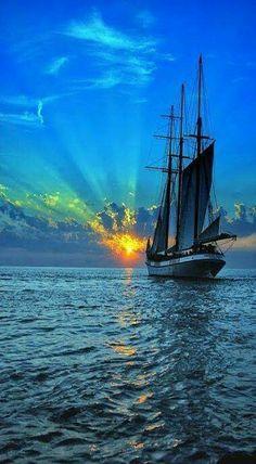 Łódż płynie po pięknym oceanie a za nią świeci zachód słońca