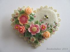 """Onto an ivory heart I added a bunch of pretty flowers and leaves, embellished with embroidery, beads and crystals...and an itty-bitty bee too! A beaded picot edging adds to the sweetness of this pin. 100% wool felt. This pin measures 2 5/8"""" across by 2 3/8"""" top to bottom. Felt Heart Brooch / Felt Heart Pin by Beedeebabee on Etsy"""