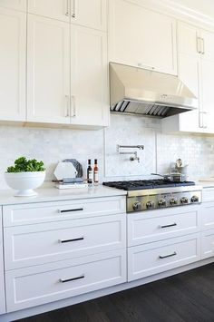 Mini brick marble backsplash graces a gorgeous white kitchen with aa stainless steel upgrades, swivel pot filler, and traditional steel vent hood. Kitchen Cabinets Decor, Kitchen Hardware, Home Decor Kitchen, Kitchen Interior, Home Kitchens, White Kitchen Backsplash, Kitchen Grey, White Cabinet Kitchen, Handles For Kitchen Cabinets